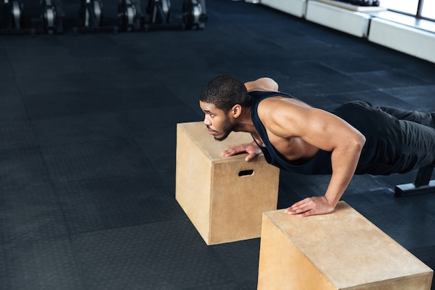Young healthy athlete doing push ups as part of bodybuilding training at the gym