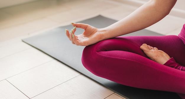 リラックスして瞑想するヨガマットの上に蓮華座に座って自宅でヨガを練習している若い健康な美しい女性。屋内と屋外のトレーニング。スポーツと健康的なアクティブなライフスタイルのコンセプト。