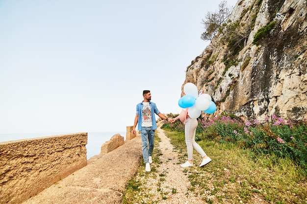 Young healthy beauty pregnant woman with her husband and balloons outdoors