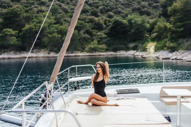 Young healthy and calm woman doing yoga on sailing yacht boat in sea at island