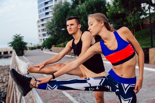 Young healthy couple doing sports exercises for legs, wearing sportswear, workout outdoors