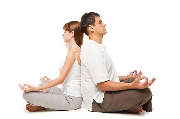 白い背景の上のヨガの位置に若い健康なカップル