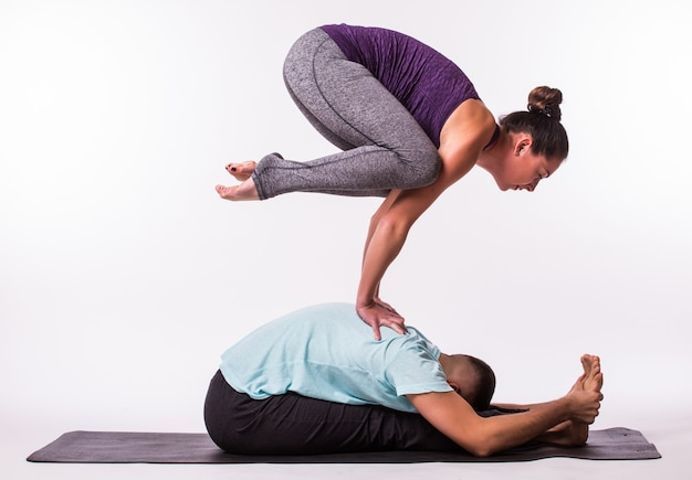 Young healthy couple man and woman in yoga position on white background