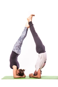 Giovani coppie in buona salute nella posizione di yoga isolata su priorità bassa bianca