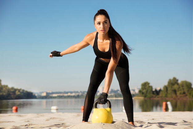 Молодая здоровая спортсменка делает тренировку на пляже