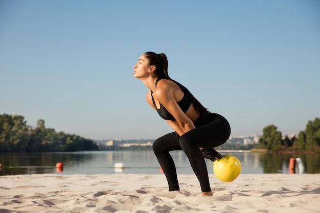 ビーチでトレーニングをしている若い健康な女性アスリート