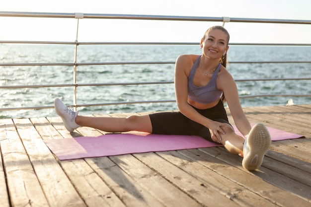 ビーチの日の出でマットの上に座っている間トレーニングの前に脚のストレッチをしている若い健康なフィットの女性