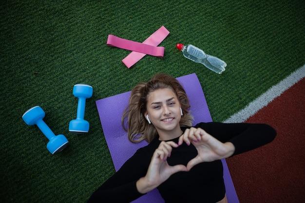 Молодая здоровая подходящая женщина отдыхает лежа на циновке. тренировки на свежем воздухе. фитнес, спортивная концепция. здоровый образ жизни