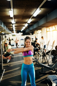 ジムで腕を伸ばして運動を開始する準備をして若い健康な柔軟な女性。