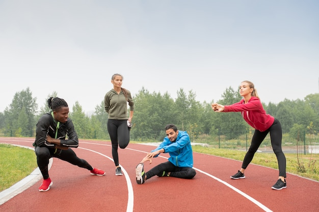 Young healthy intercultural men and women in sportswear doing physical exercises on outdoor stadium