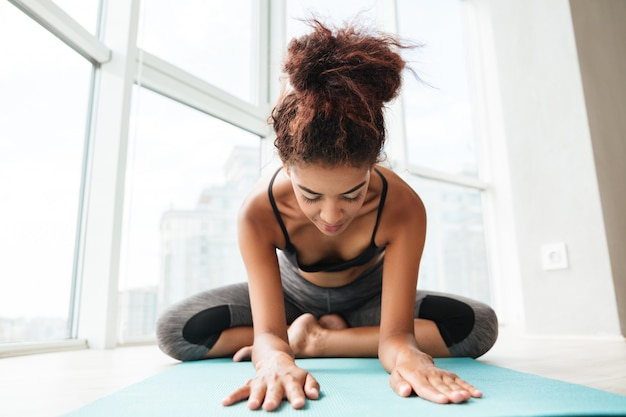 Young healthy lady sitting in lotus pose and making exercise