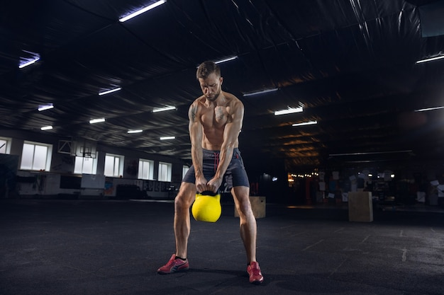 Young healthy male athlete doing exercises in the gym