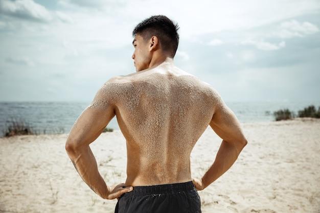 ビーチで運動をしている若い健康な男性アスリート。晴れた日の川沿いでのサイン男性モデル上半身裸のトレーニング空気。健康的なライフスタイル、スポーツ、フィットネス、ボディービルの概念。