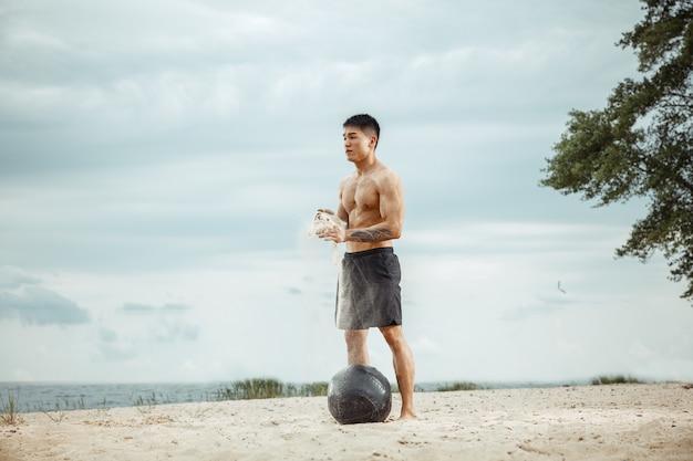 Молодой здоровый спортсмен-мужчина делает упражнения с мячом на пляже