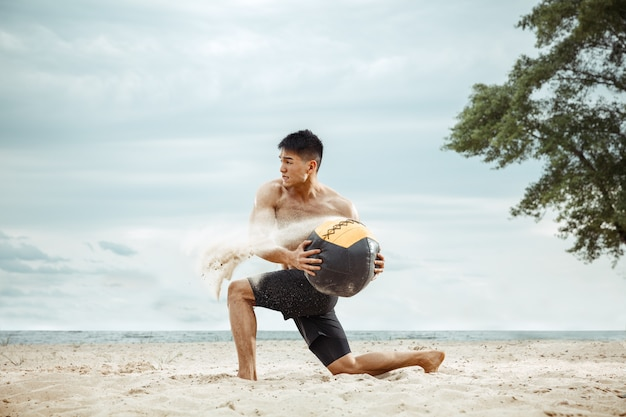 Young healthy man athlete doing exercise with ball at the beach. signle male model shirtless training air at the river side in sunny day. concept of healthy lifestyle, sport, fitness, bodybuilding.