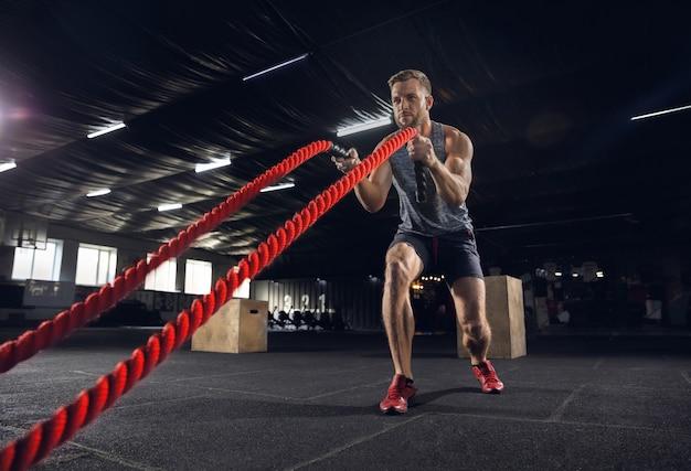 若い健康な男、ジムでロープを使って運動をしているアスリート。一生懸命練習し、上半身を鍛える独身男性モデル。健康的なライフスタイル、スポーツ、フィットネス、ボディービル、幸福の概念。