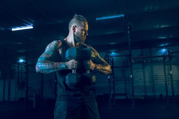 Молодой здоровый спортсмен человек упражнения с весами в тренажерном зале. одинокий мужчина-модель усиленно тренирует верхнюю часть тела, тренируется. концепция здорового образа жизни, спорта, фитнеса, бодибилдинга.