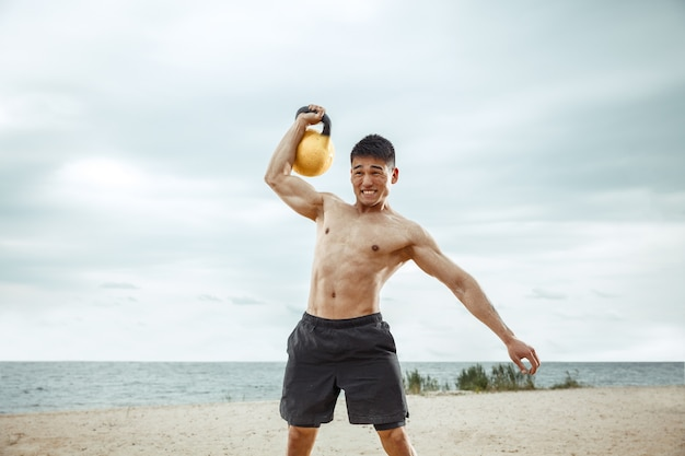 Young healthy man athlete doing exercise with the weight at the beach. signle male model shirtless training at the river side in sunny day. concept of healthy lifestyle, sport, fitness, bodybuilding.