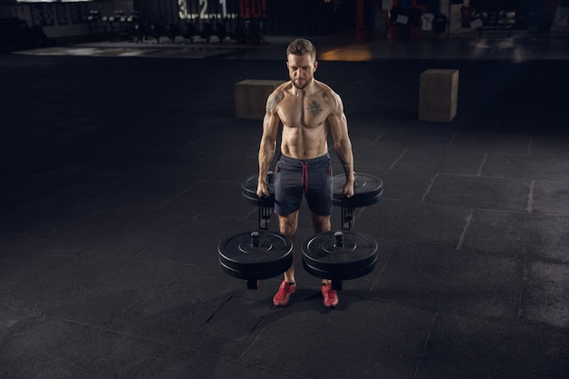 Young healthy man, athlete doing exercises, posing with barbell in gym
