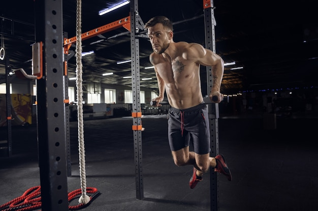 Young healthy man, athlete doing exercises, pull-ups in gym. single male model practicing hard and training his upper body. concept of healthy lifestyle, sport, fitness, bodybuilding, wellbeing.