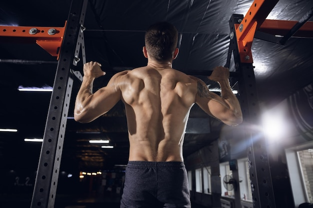 Young healthy man, athlete doing exercises, pull-ups in gym.