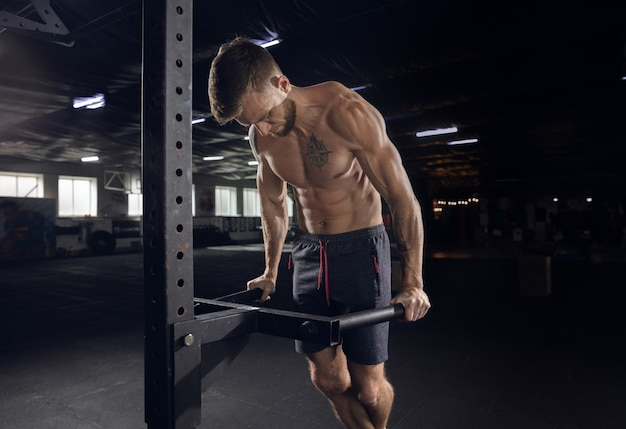 Giovane uomo in buona salute, atleta che fa esercizi, pull-up in palestra
