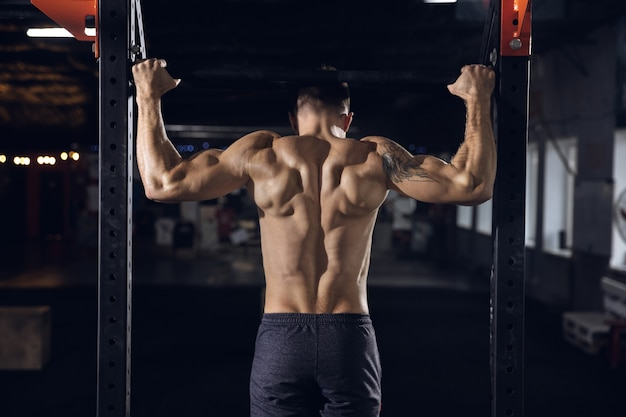 Young healthy man, athlete doing exercises, pull-ups in gym