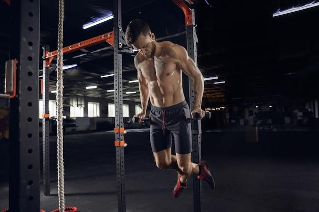 젊은 건강한 남자, 운동을하는 운동 선수, 체육관에서 턱걸이. 열심히 연습하고 상체를 훈련하는 단일 남성 모델. 건강한 라이프 스타일, 스포츠, 피트니스, 보디 빌딩, 웰빙의 개념.