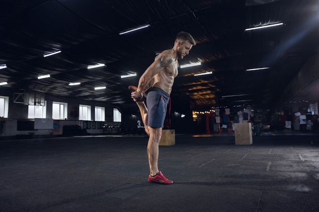 Young healthy man, athlete doing exercises, stretching in gym. single caucasian model practicing hard, training his body. concept of healthy lifestyle, sport, fitness, bodybuilding, wellbeing.