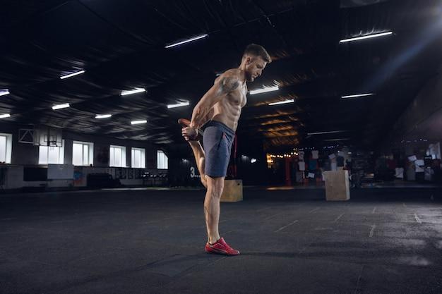 건강 한 젊은이, 운동을하는 운동 선수, 체육관에서 스트레칭. 열심히 연습하고 그의 몸을 훈련하는 단일 백인 모델. 건강한 라이프 스타일, 스포츠, 피트니스, 보디 빌딩, 웰빙의 개념.