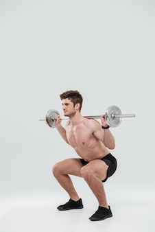 Young healthy man athlete doing exercises with barbell