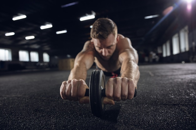 Young healthy man, athlete doing exercises with the roller in gym. single male model practicing hard and training his upper body. concept of healthy lifestyle, sport, fitness, bodybuilding, wellbeing.