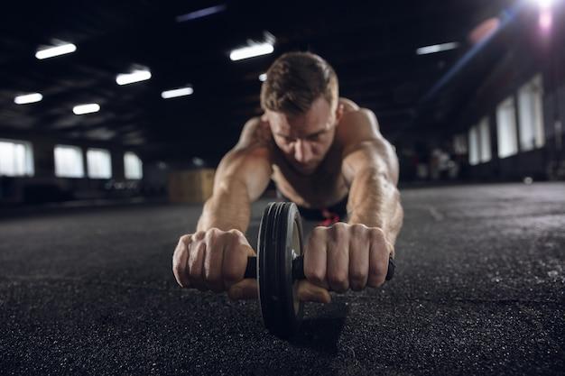 若い健康な男性、ジムでローラーを使って運動をしている運動選手。懸命に練習して上半身を鍛える独身男性モデル。健康的なライフ スタイル、スポーツ、フィットネス、ボディービル、幸福の概念。