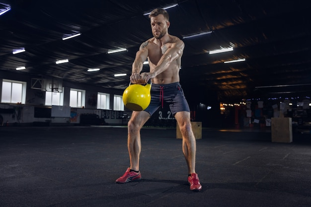 若い健康な男性、ジムで体重を使って運動をしている運動選手。 1 人の白人モデルが一生懸命練習し、体を鍛えています。健康的なライフ スタイル、スポーツ、フィットネス、ボディービル、幸福の概念。