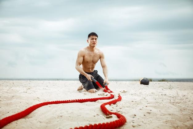 해변에서 라오 하 고 건강 한 젊은이 선수