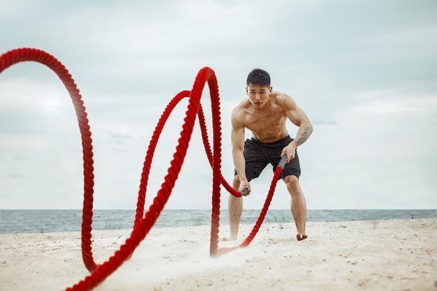 ビーチでスクワットをしている若い健康な男性アスリート