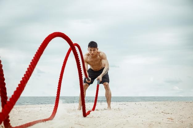 Atleta giovane uomo sano facendo squat in spiaggia