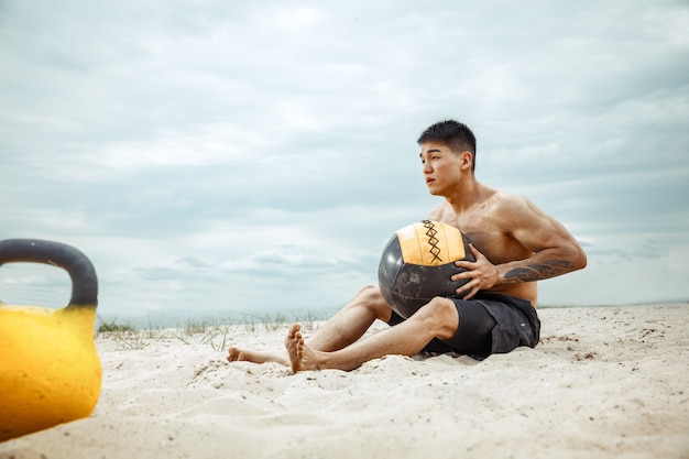 Young healthy man athlete doing squats at the beach