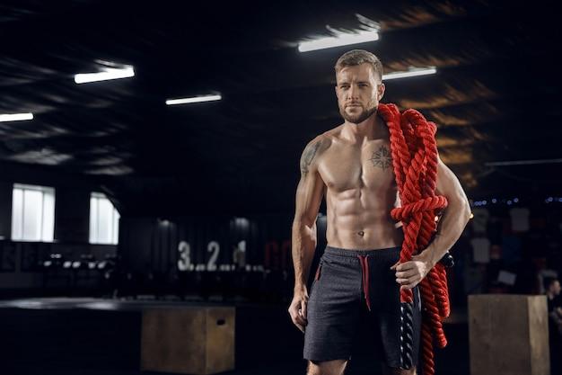 Молодой здоровый человек, спортсмен, уверенно позирует с веревками в тренажерном зале.