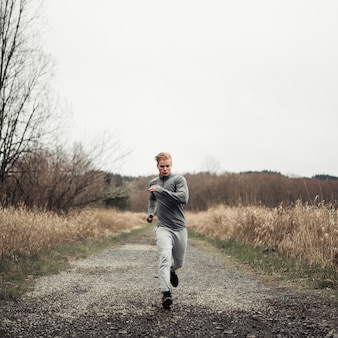 Young healthy man running on the dirt road