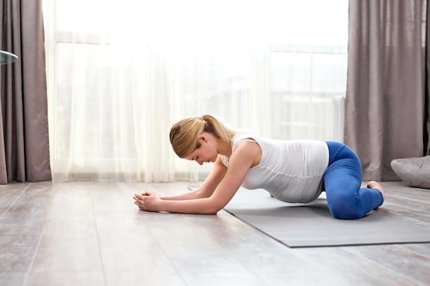 Молодая здоровая беременная женщина делает упражнения на полу дома в одиночестве