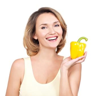 La giovane donna sorridente in buona salute tiene il pepe - isolato su bianco.