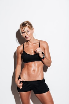 Young healthy sportswoman posing while standing