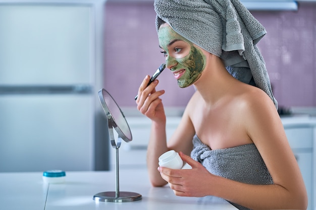 Young healthy woman in bath towel applying cleansing face clay mask after shower during spa day at home using brush and small round table mirror. face skin care