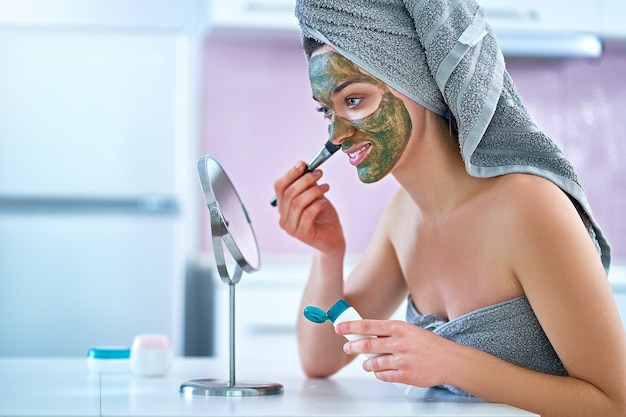 Young healthy woman in bath towel applying green face clay mask after shower during spa day at home using brush and small round table mirror. face skin care