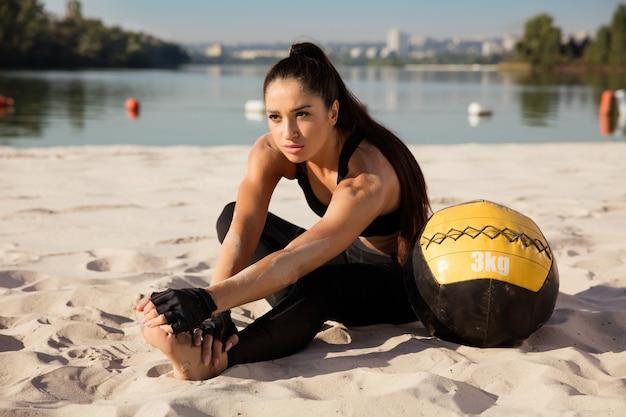 해변에서 공 운동을 하 고 젊은 건강 한 여자
