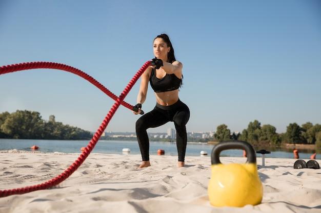 Giovane donna in buona salute che fa esercizio con le corde in spiaggia.