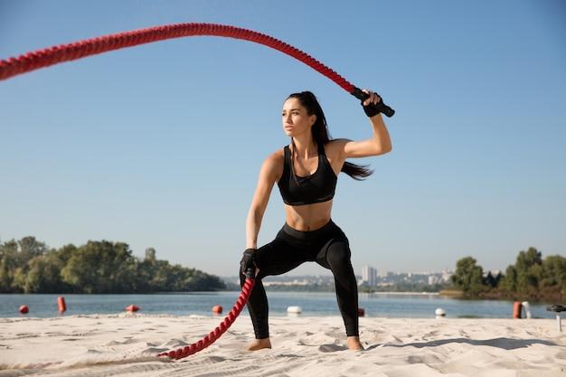 Молодая здоровая женщина упражнения с веревками на пляже.