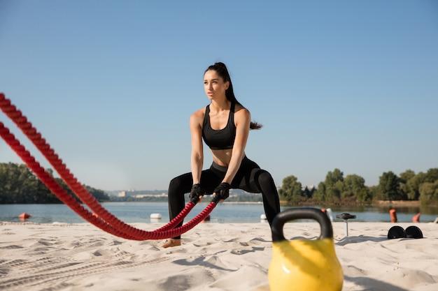 해변에서 로프와 함께 운동을 하 고 젊은 건강 한 여자.