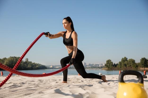 해변에서 로프와 함께 운동을 하 고 젊은 건강 한 여자